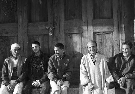 Enade leenden. MC Kash 2012. Kashmiriska män utanför en gammal nedstängd butik. Ofta en mötesplats för vänner att prata och röka. Foto MC Kash.