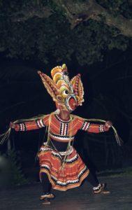 En djävulsdansare med demonmask. Maskerna är ofta porträtt av olika populära demoner och andra gudomligheter i lankesisk folktro. Image credits: Wikimedia.org