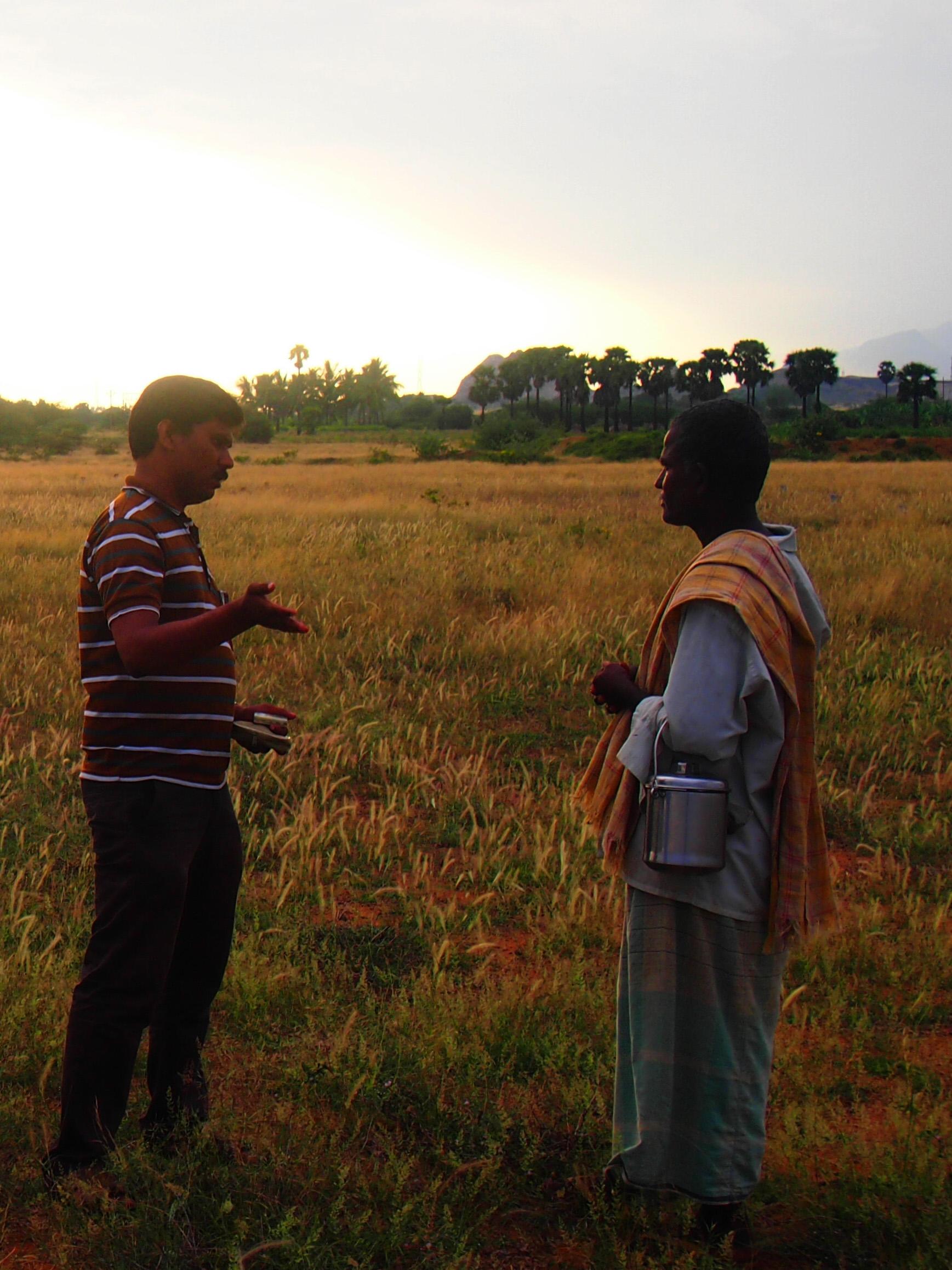 Mathivanan, fältstationskoordinator på ATREEs fältstation ACCC, gör en spontan intervju med en herde i fält. Foto; Patrick Wennström