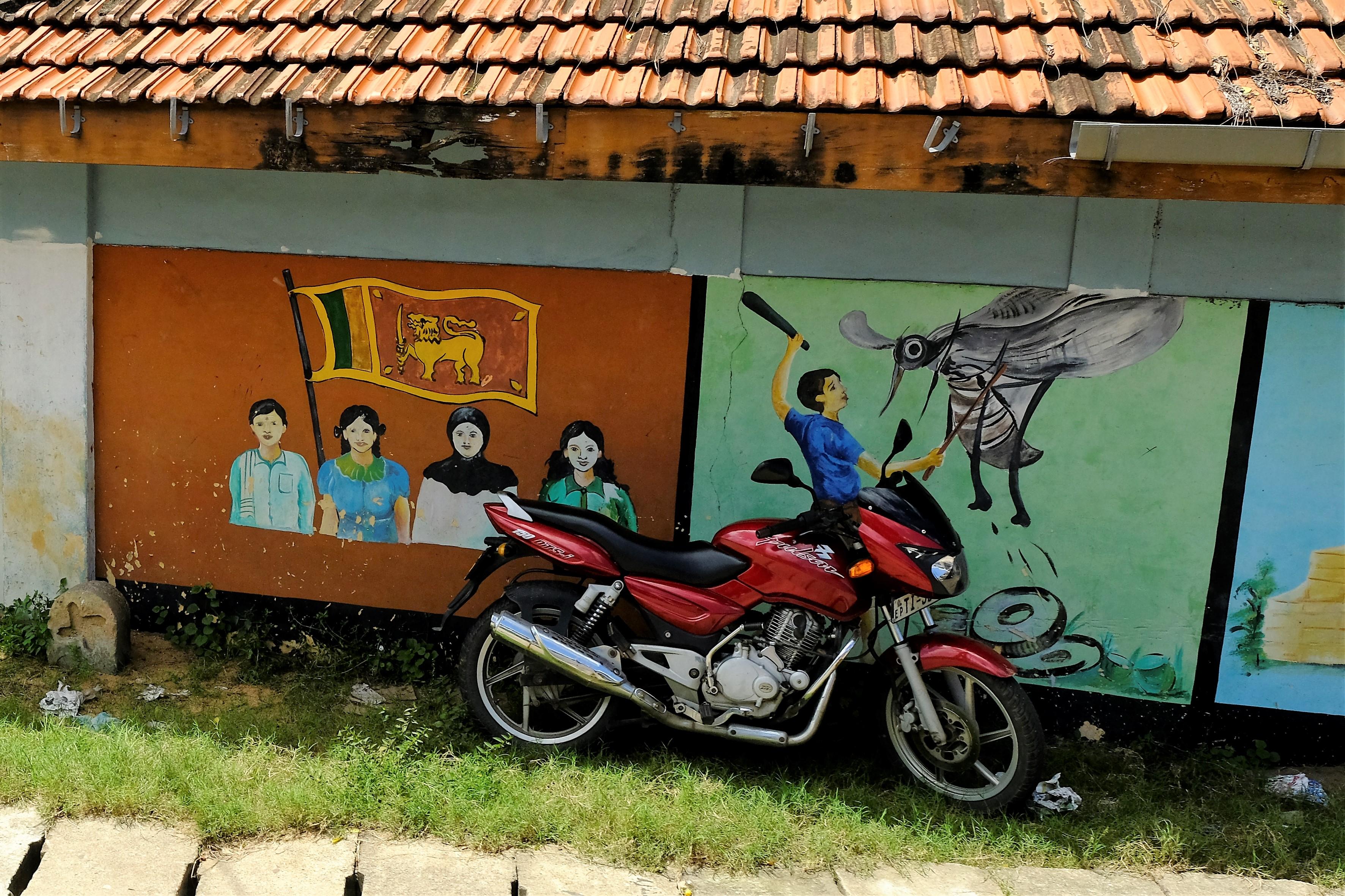 Pedagogiska målningar om samförstånd mellan folkgrupper och kamp mot sjukdomsbärande myggor. Samt en lämplig plats i skuggan att ställa motorcykeln. Foto: Johan Mikaelsson