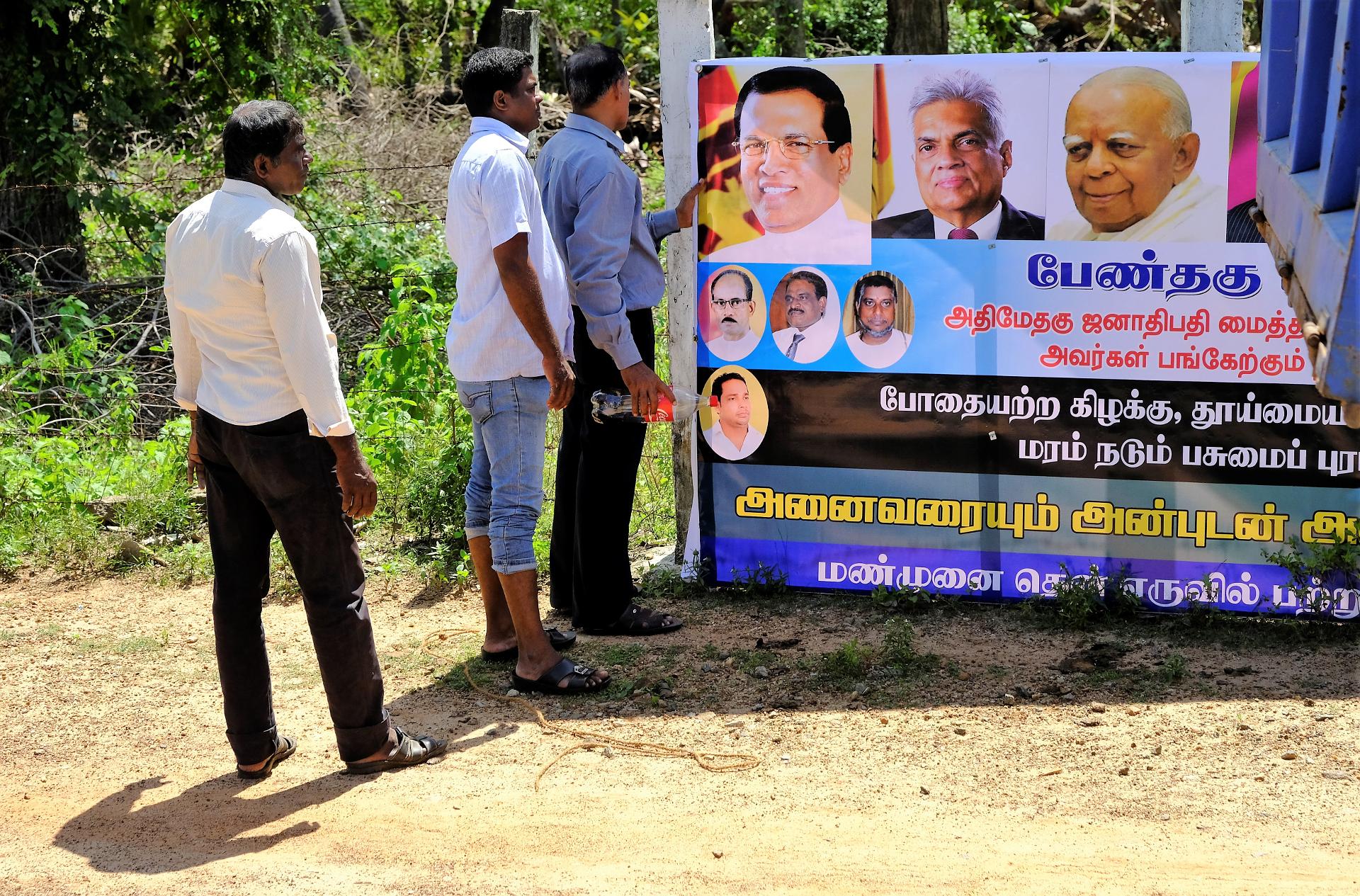 Några män, sannolikt från säkerhetstjänsten, inspekterar en skylt som vandaliserats inför presidentens besök i östra Sri Lanka några dagar senare. På skylten syns president Maithripala Sirisema, premiärminister Wickremesinghe och R. Sampanthan, ledare för Tamilska nationella alliansen. Foto: Johan Mikaelsson