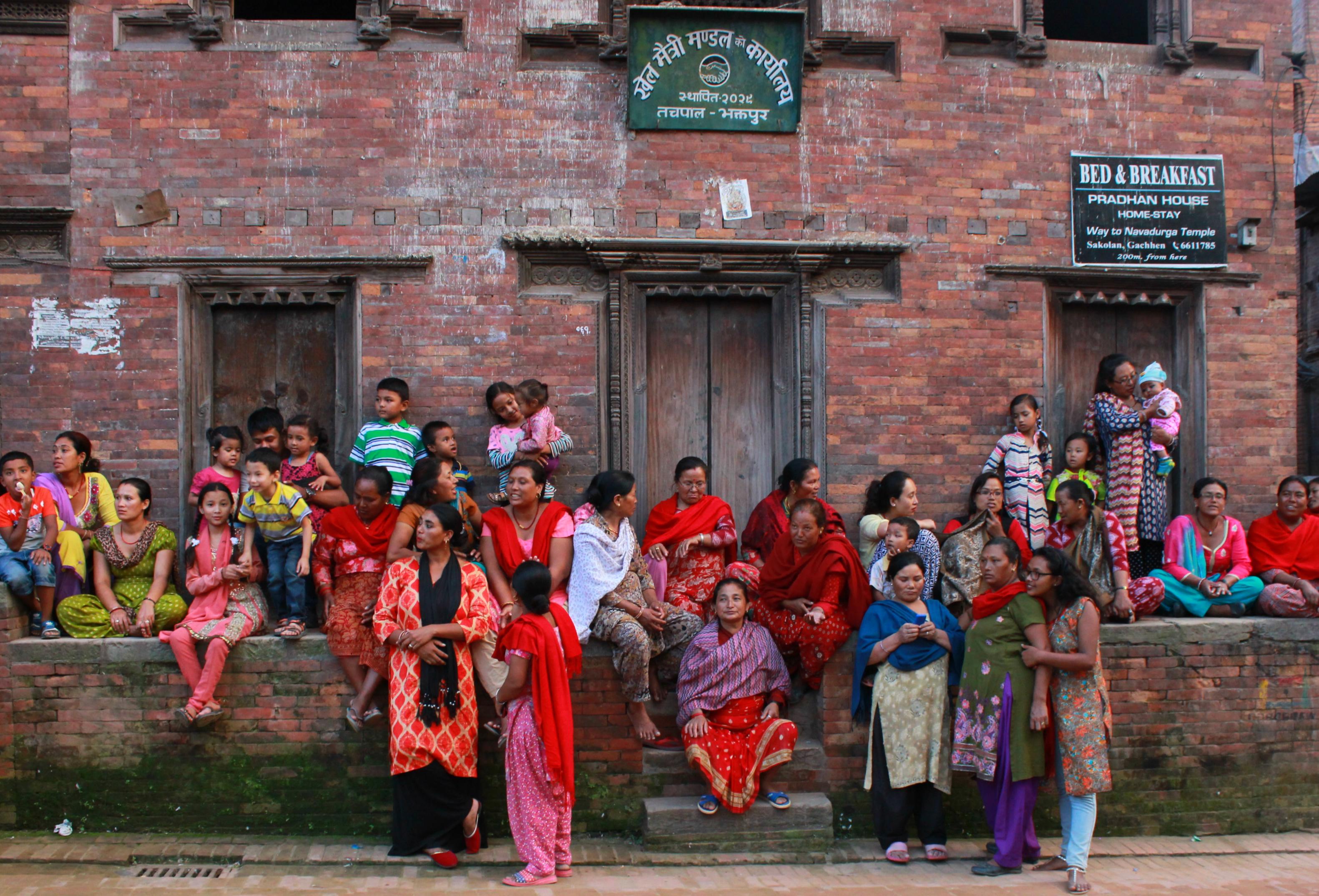 """Kvinnor och barn på ett av Bhaktapurs torg i väntan på att festivalen """"Indra Jatra"""" ska börja. Den åtta dagar långa festivalen firar att monsunperioden är över i Nepal. Foto: Celia Boltes"""
