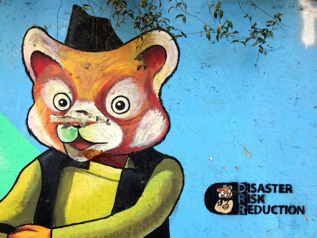 """Muren längst med """"Drömmarnas trädgård"""" i centrala Kathmandu är fylld med målningar som relaterar till jordbävningskatastrofen 2015. Foto: Celia Boltes"""