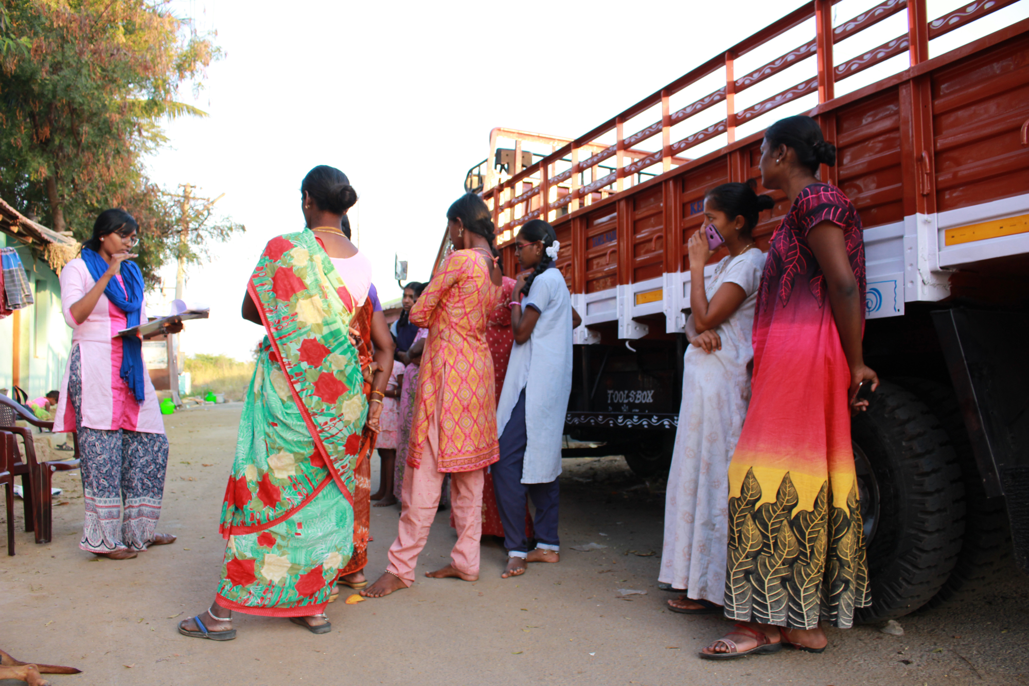 Elizabeth pratar mens med kvinnor i en fokusgrupp i ett slumområde