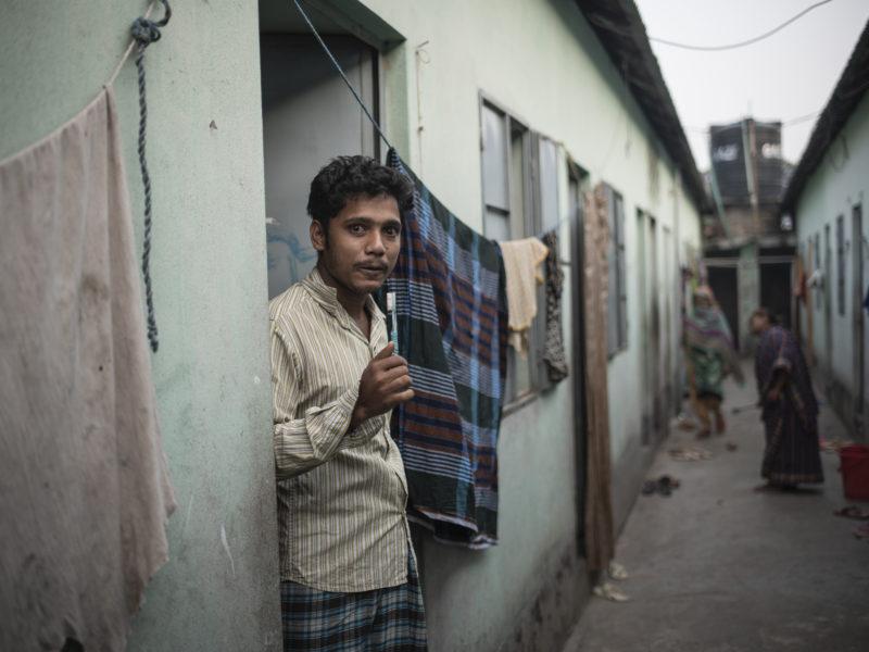 Ashikuzzman Rubel står ute mellan några hus och borstar sina tänder. Foto Troy Enekvist