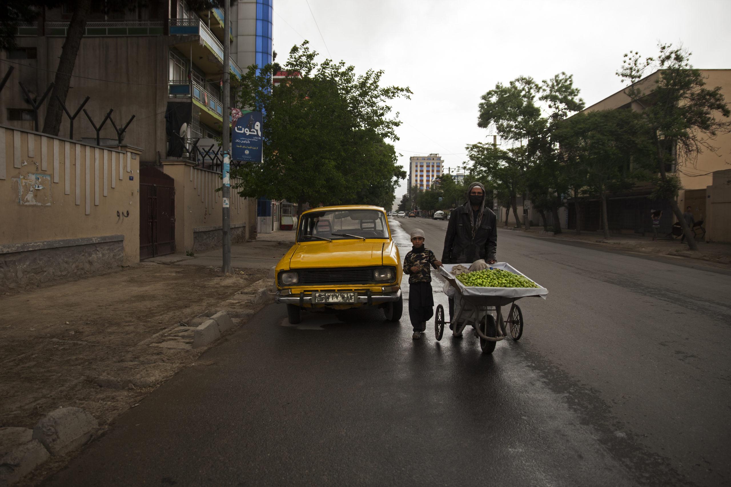 Fruktförsäljare med sitt barn i Kabul, Afghanistan.