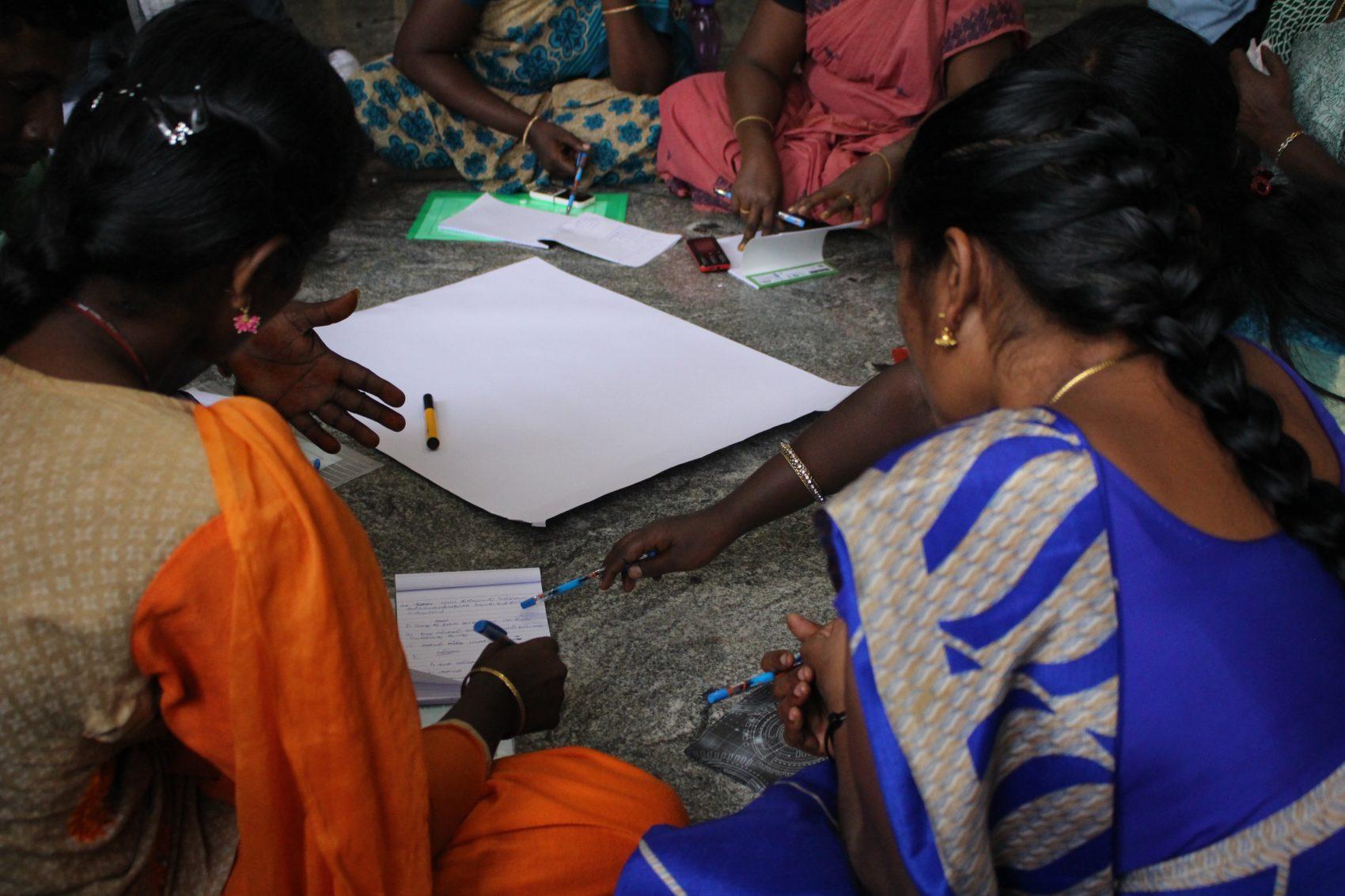 Kvinnor sitter i en cirkel på golvet med papper och diskussionsunderlag i mitten.