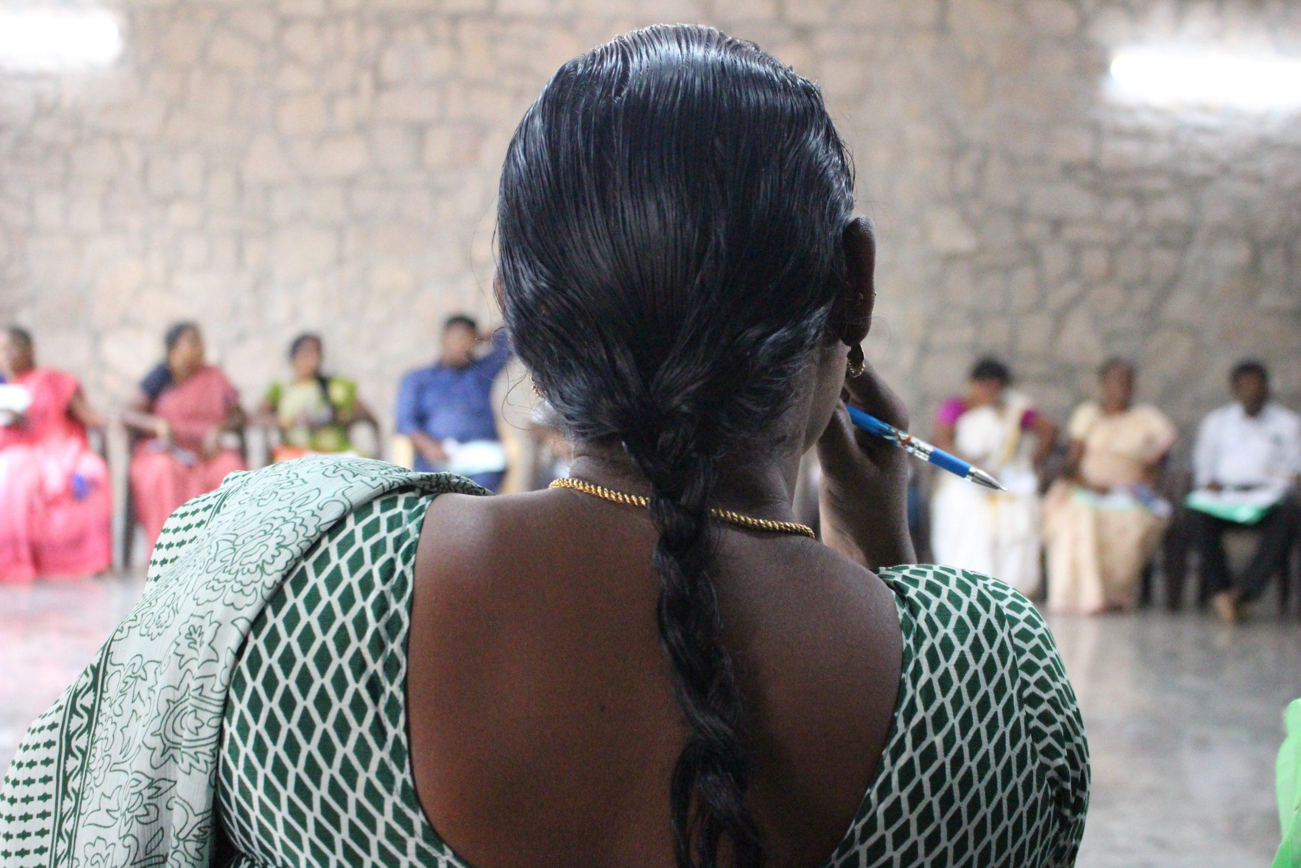 Indisk kvinna sitter med ryggen mot kameran. Hon delat på en workshop kring mänskliga rättigheter i Indien.
